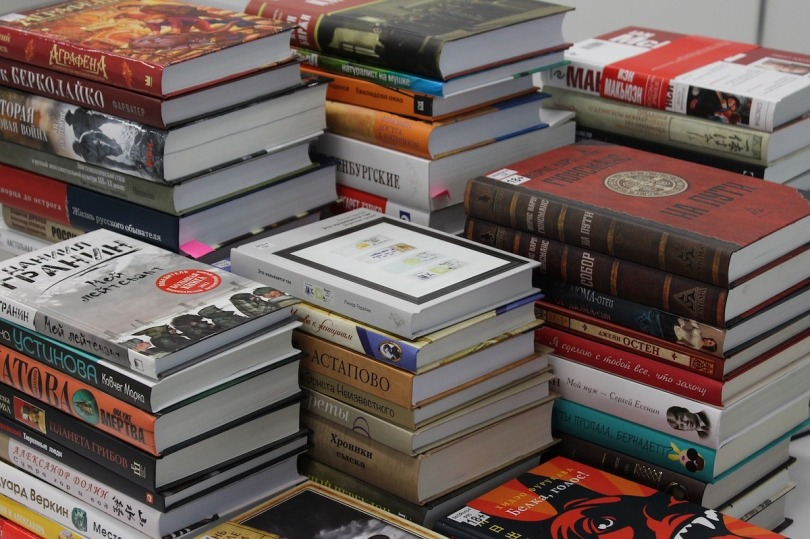 An assorted selection of books stacked in piles