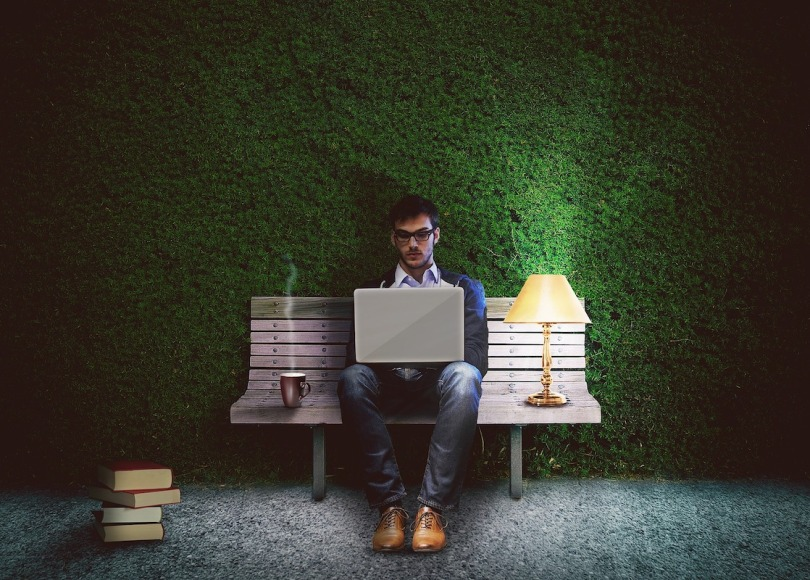 A man sat on a bench with a laptop in front of a green background