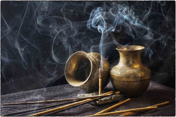 Incense burning next to gold containers