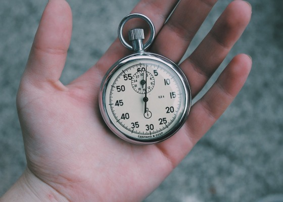 An open hand holding a large stopwatch