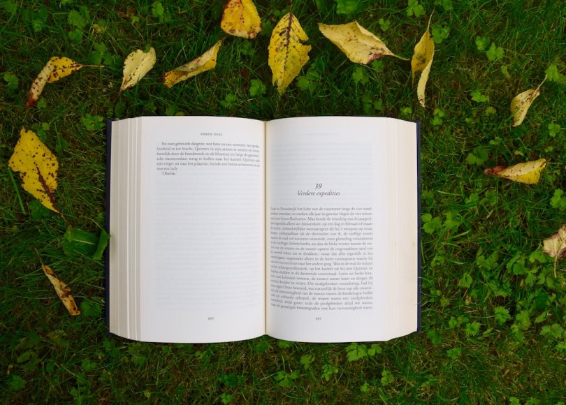 An open book on green grass surrounded by leaves