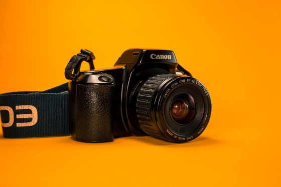 A Canon camera with an orange background