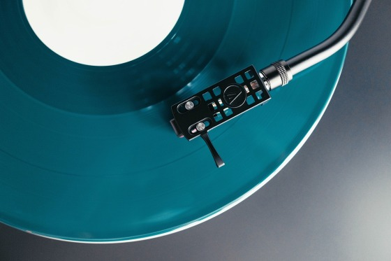 A stylus on a turquoise blue record