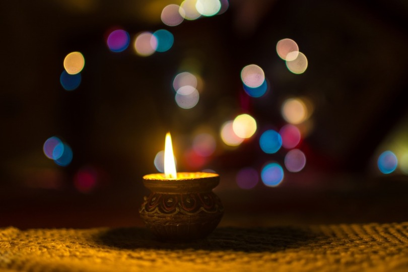 A ornate candle with small coloured circles of light in the background