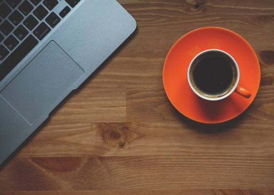 An orange cup containing black coffee next to a MacBook