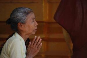 An older woman praying