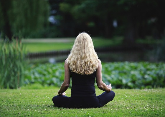 A woman with blonde hair sat in a park meditating