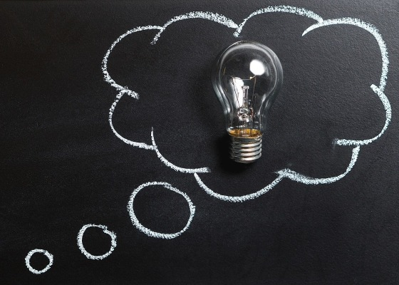 Thought bubbles on a blackboard with a lightbulb
