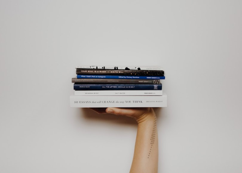 A hand holding some books