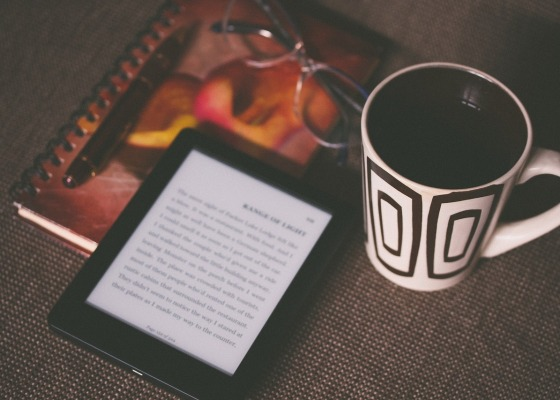 A Kindle, a coffee mug, a notebook, and a pair of glasses