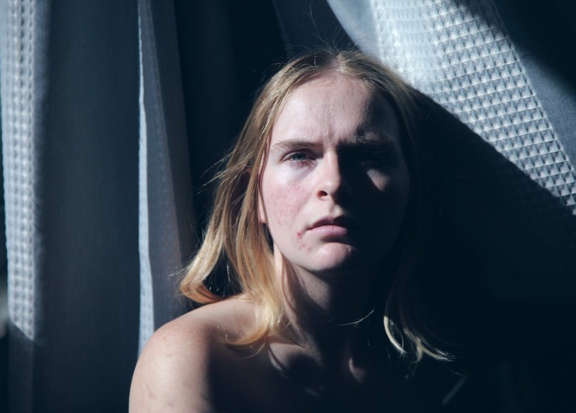 A lady looking depressed with sunlight shining on her face