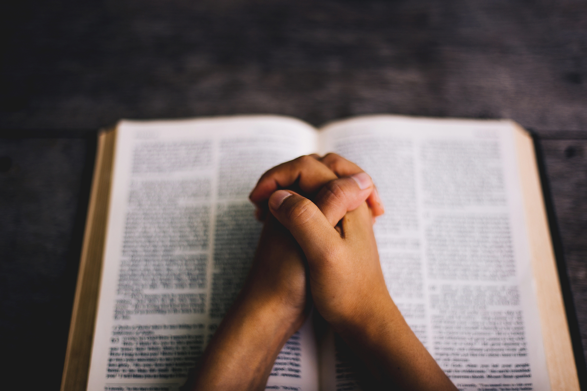 A man's hands clasped in prayer resting upon an open Bible