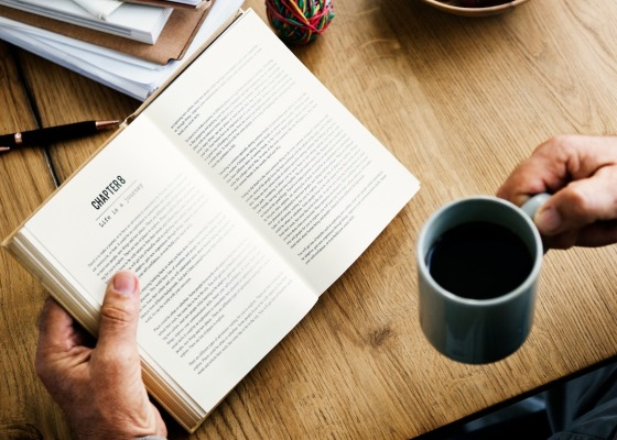 An open book and a mug of black coffee