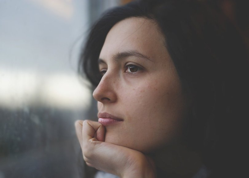 A woman with her hand on her chin looking contemplative