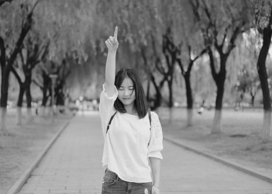 Girl pointing upwards black and white