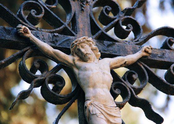 A figure of Jesus hanging on a metal ornamental cross.