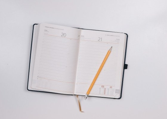 An open notebook and pencil on a white background