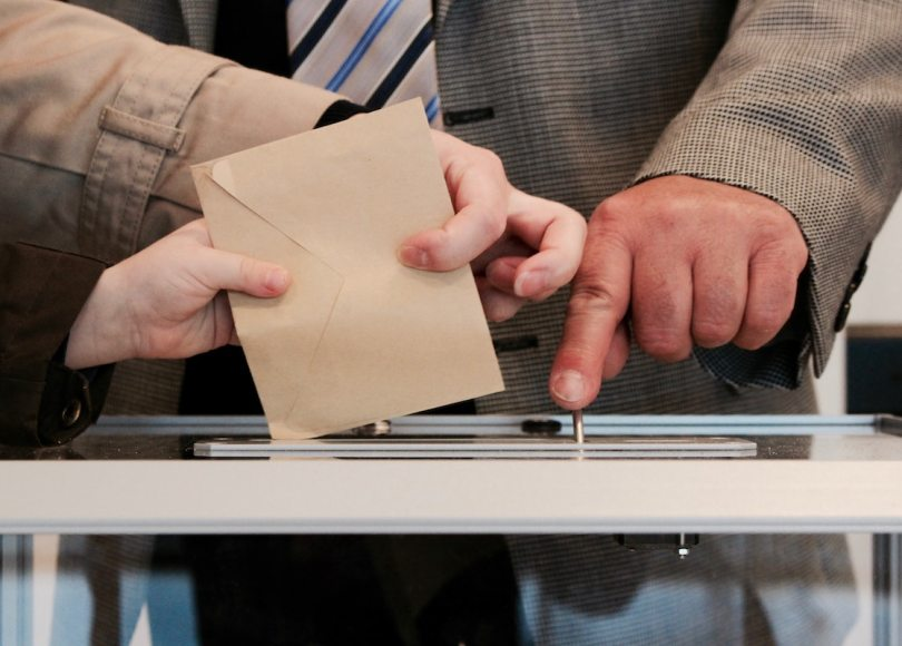Someone posting an envelope into a box at a polling station