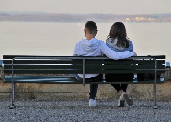 A young couple sitting on a bench looking out into the sea