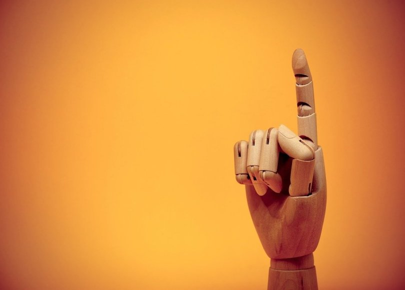 A wooden hand pointing upwards on an orange background
