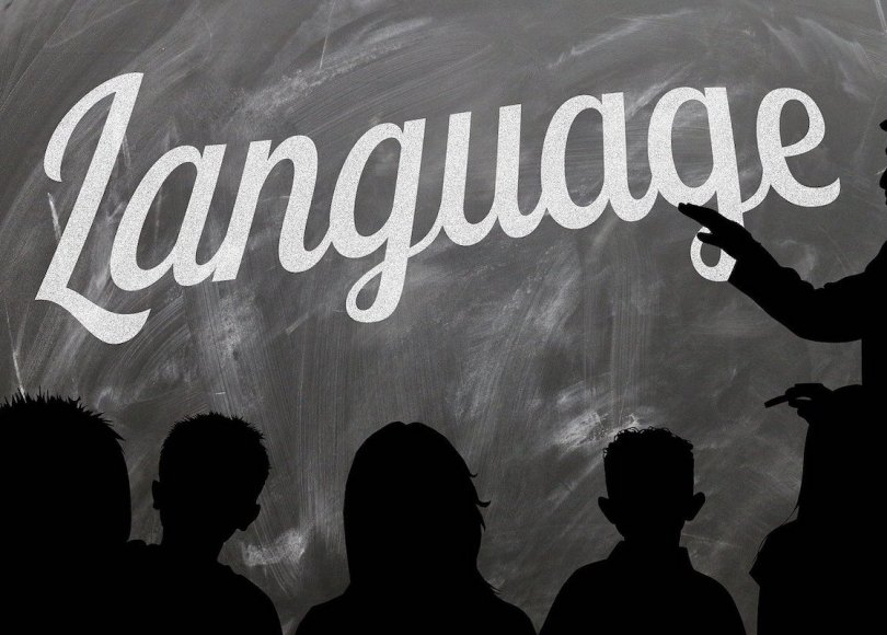 A blackboard displaying the word 'Language' with students in silhouette looking on