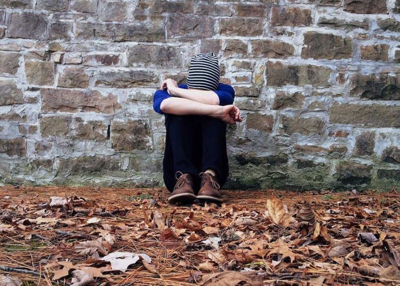 A person hunched up against a brick wall looking sad