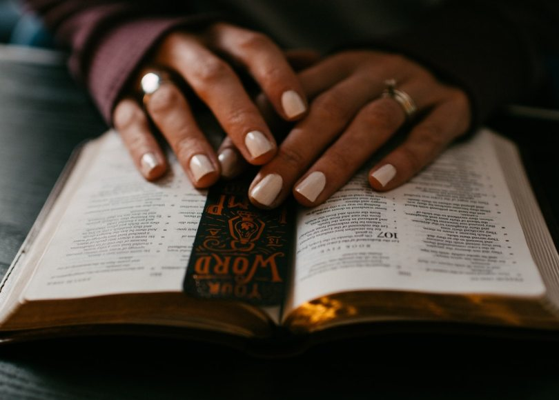 A close-up of a person's hands and varnished nails as they read the Bible