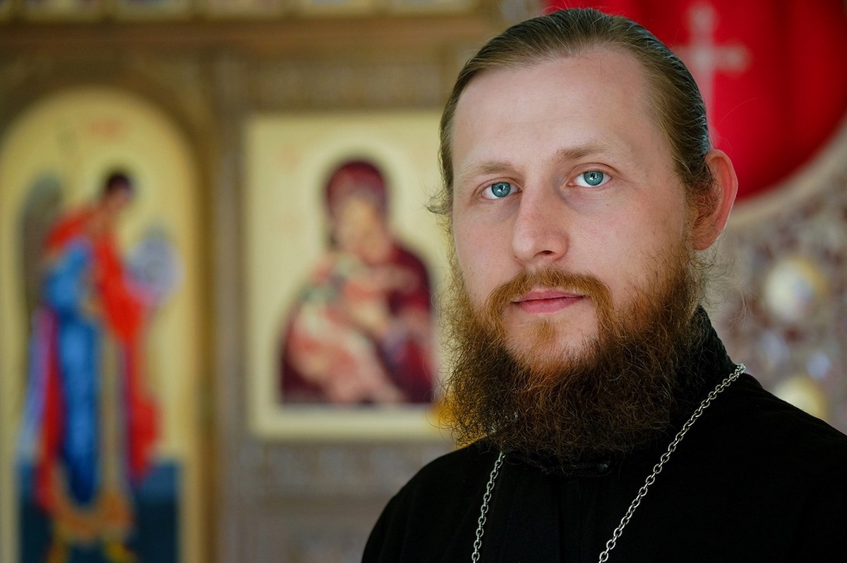A priest wearing a black garment and looking serious