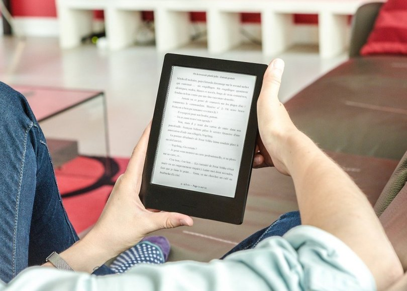 A person sat on a sofa reading on an eReader