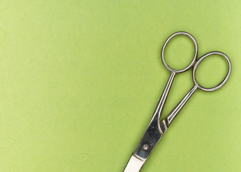 A pair of scissors on a green background