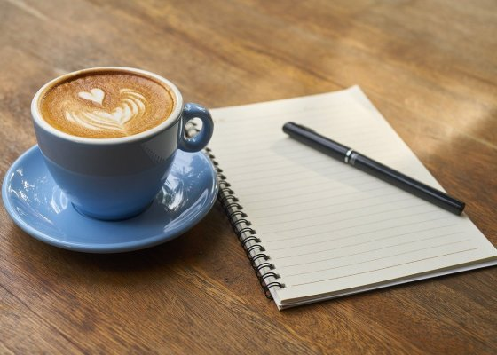 A notepad and pen next to a cup of coffee