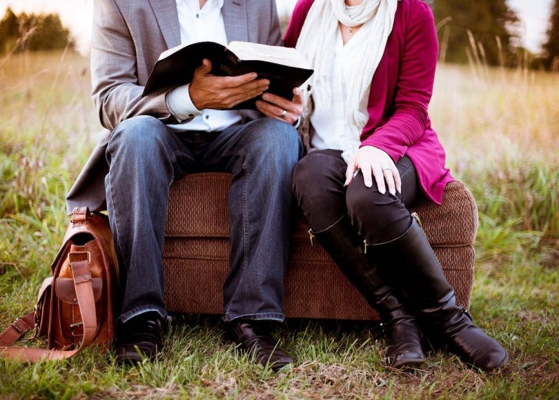 A couple sat on in a field reading the Bible
