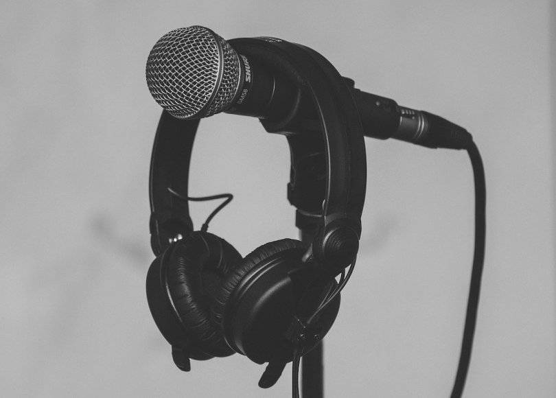 A black and grey photo of some headphones hanging on a microphone
