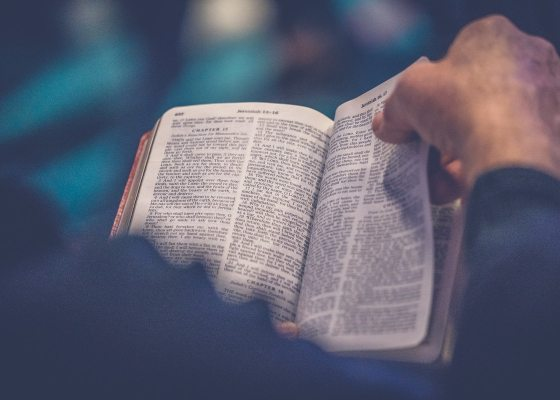 A closeup of a man leafing through the Bible
