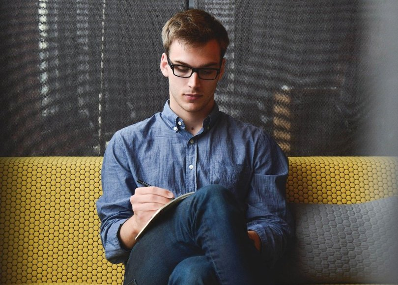 A man wearing glasses sat on a sofa writing
