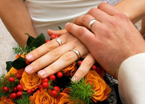 A man holding a woman's hand and both are wearing wedding rings