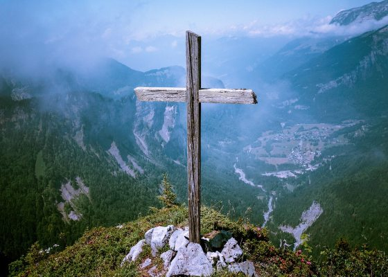 A wooden cross in an open landscape