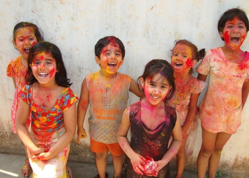 A group of Indian children covered in paint, smiling