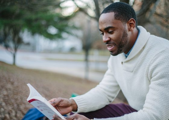 A black man reading a book in a park