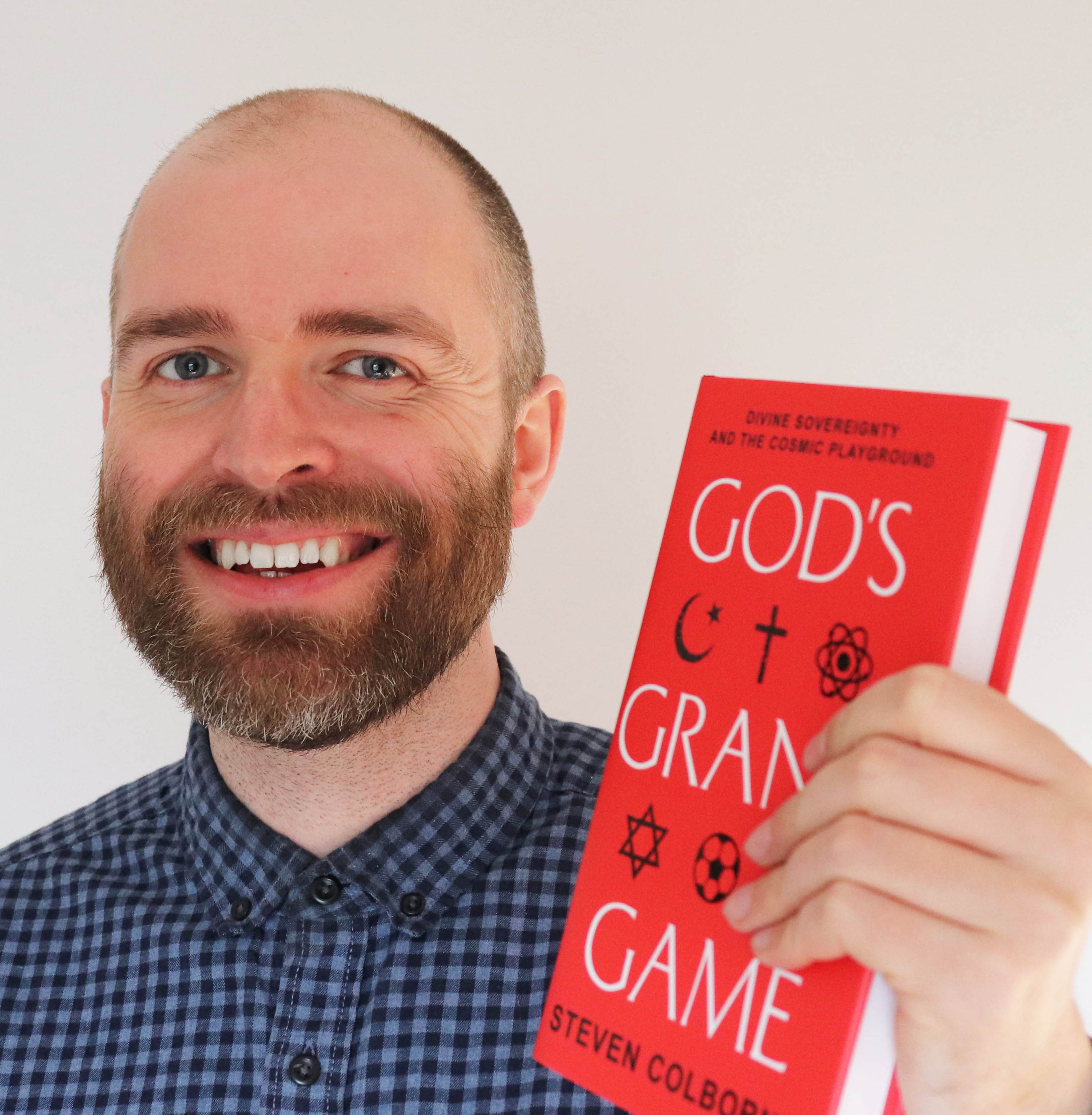 Steven Colborne holding a copy of God's Grand Game