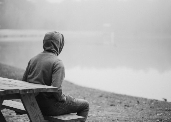 Man with hood on bench black and white