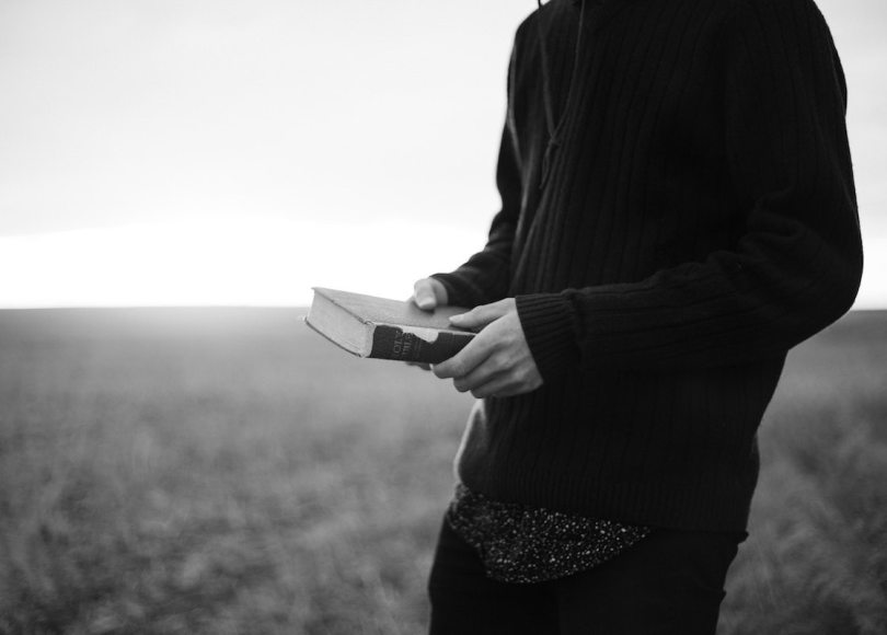 Person holding a Bible black and white
