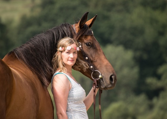 Woman stood next to a brown horse