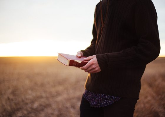 Man holding a Bible in a field
