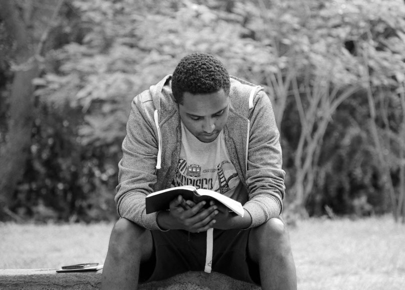 Man reading Scripture in park black and white