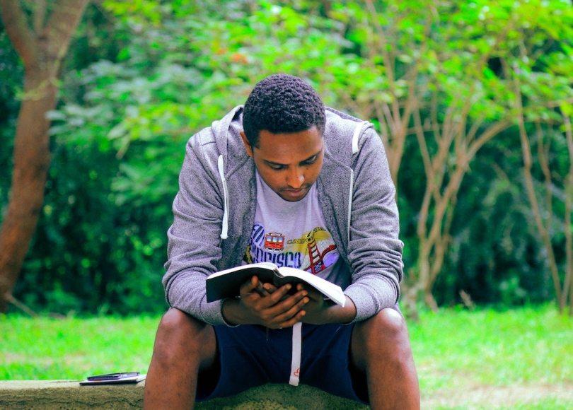 Man reading Scripture in park