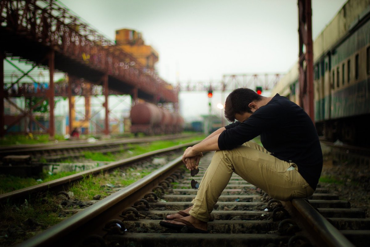 Man sitting on a train track looking depressed