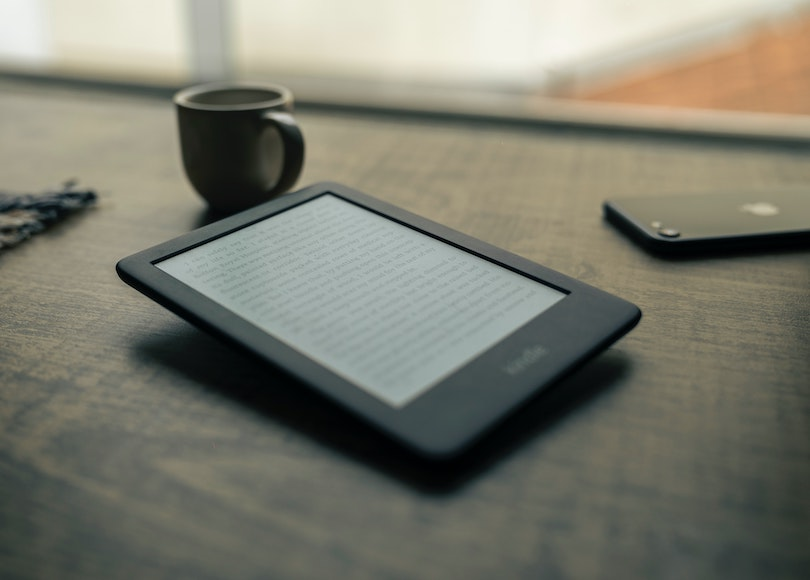 Kindle and mug of coffee