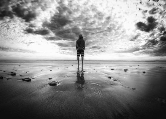 Man looking towards ocean black and white
