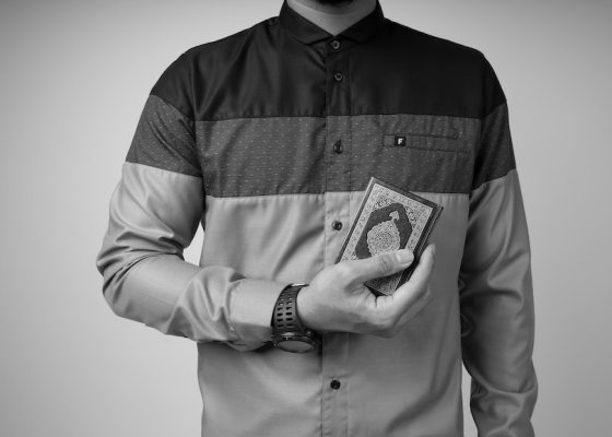 Person holding Quran black and white
